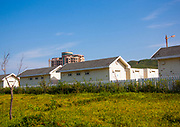 KUMGANG<br /> THE NORTH KOREAN GHOST TOWN<br /> <br /> The first town USA will find on his way to invade NK will be this ghost town where HUnday lost 1 billion USD..<br /> <br /> The Mount Kumgang tourist complex in North Korea, near the DMZ, was built in 1998 by the South Korean giant company Hyundai. The chaebol paid a fee of $1 billion to the North Korean government for 50 years of exclusivity. The cost of the 500-square kilometer complex was $400 million, including hotels, a spa, a fire station, a tourism office, a golf course, a supermarket, a clinic, tours in the mountain... Kumgang resort attracted nearly 2 millions south korean tourists from1998 to 2008.<br /> In July 2008 a South Korean tourist, Miss Park Wang-ja, was shot dead there and South Korea decided to stop all the tours in North Korea. The North Korean government said the tourist entered the military zone, and ignored the warnings from the north korean soldiers.<br /> So in retaliation, North Korea decided to seize the whole tourist complex. This decision was a real drama. Not for the touristic industry only, but for the separated families from the south and the north: Kumgang was also the place where hundreds of North and South Korean relatives were meeting each other for the first time in decades.<br /> For those reasons, since 2008, Mount Kumgang complex has became a ghost town. Only very few western tourists could visit the area.<br /> <br /> Photo shows:    Few houses are along the road. My guides explains that they have been seized by the North Korea government when South Korea did not keep its commitments. A classic way to rewrite History in North Korea!<br /> ©Eric Lafforgue/Exclusivepix Media