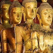 A line of Buddha statues at Wat Mai Suwannaphumaham.  Wat Mai, as it is often known, is a Buddhist temple in Luang Prabang, Laos, located near the Royal Palace Museum. It was built in the 18th century and is one of the most richly decorated Wats in Luang Prabang.