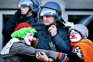 Titusinder af aktivister marcherede lørdag d.12. december 2009 fra Christiansborg til Bellacentret på Amager i anledning af klimatopmødet COP15. To aktivister udklædt som klovne krammer en kampklædt betjent.