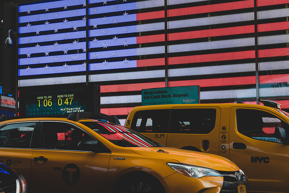 Taxi cabs lined up in front of the illuminated flag in Times Square.
