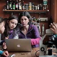 Nederland, Amsterdam , 31 maart 2015.<br /> Elisabeth Erasmus geeft haar kinderen thuis onderwijs.<br /> op de foto moeder elisabeth geeft dochter Malaika les vanachter de laptop. dochter Maya kijkt door een microscoop.<br /> Foto:Jean-Pierre Jans