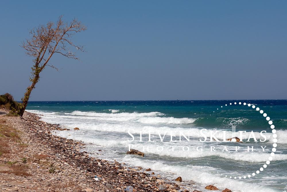 Samos. Greece. Waves of the Aegean Sea splash into the pebbly shoreline near the northern coastal town of Agios Konstantinos.