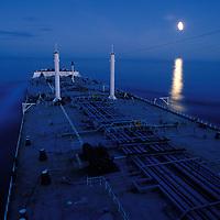 USA, Alaska, Oil tanker Arco Juneau sails off coast of southeast Alaska past rising full moon