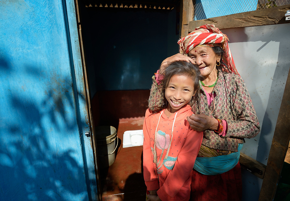 Pamfa Maya Pulami and her granddaughter pose in front of a latrine in Salang, a village in the Dhading District of Nepal where Dan Church Aid, a member of the ACT Alliance, has provided a variety of support to local villagers in the wake of a devastating 2015 earthquake. The village's water system was destroyed by the quake, forcing women to walk two hours or more to a nearby river to fetch water. Working with a local organization, the Forum for Awareness and Youth Activity, the ACT Alliance rebuilt the village's water system and installed new latrines for residents.