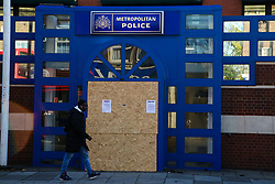 © Licensed to London News Pictures. 12/11/2020. London, UK. A man walks past the entrance to Edmonton Police Station in north London which is boarded up following an incident where a vehicle was driven into the police station just before 7pm on Wednesday, 11 November. A 45-year-old man left the vehicle before attempting to set fire to it using petrol. He was arrested by officers on suspicion of arson and is remanded in custody. The incident is not being treated as terror-related. Photo credit: Dinendra Haria/LNP