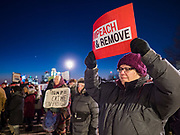 """17 DECEMBER 2019 - DES MOINES, IOWA: A woman carries an """"Impeach and Remove"""" sign in front of the Iowa State Capitol. About 300 people came to the Iowa State Capitol in Des Moines in near freezing weather to call for the impeachment of President Donald Trump. The rally, and others like it around the US, come on the eve of an impeachment vote in the US House of Representatives.          PHOTO BY JACK KURTZ"""