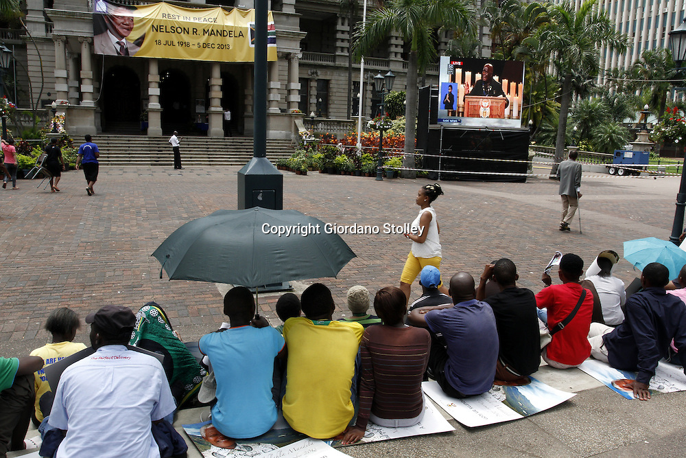 DURBAN - 15 December 2013 - Mourners watch the funeral of Nelson Mandela outside the Durban City Hall as it was broadcast live on big screens from Qunu where the international icon was laid to rest. Picture: Allied Picture Press/APP