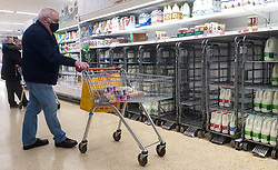 © Licensed to London News Pictures. 08/10/2021. London, UK. A shopper looks at nearly empty shelves of fresh milk in Sainsbury's, north London. The Government and retailers warn that food and fuel shortages could continue until Christmas due to labour shortages following Brexit. Photo credit: Dinendra Haria/LNP