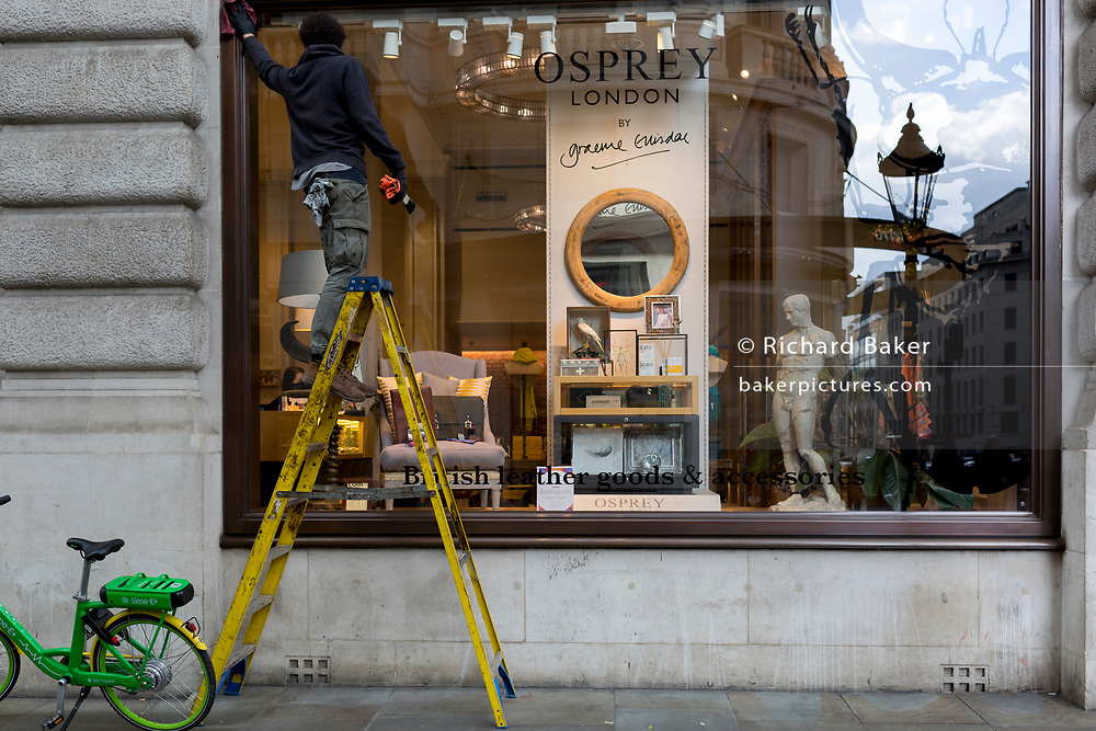 Above a statue of the ancient Greek God Apollo, a contract window cleaner wipes window glass of Osprey in Lower Regent Street, on 2nd May 2019, in London, England.