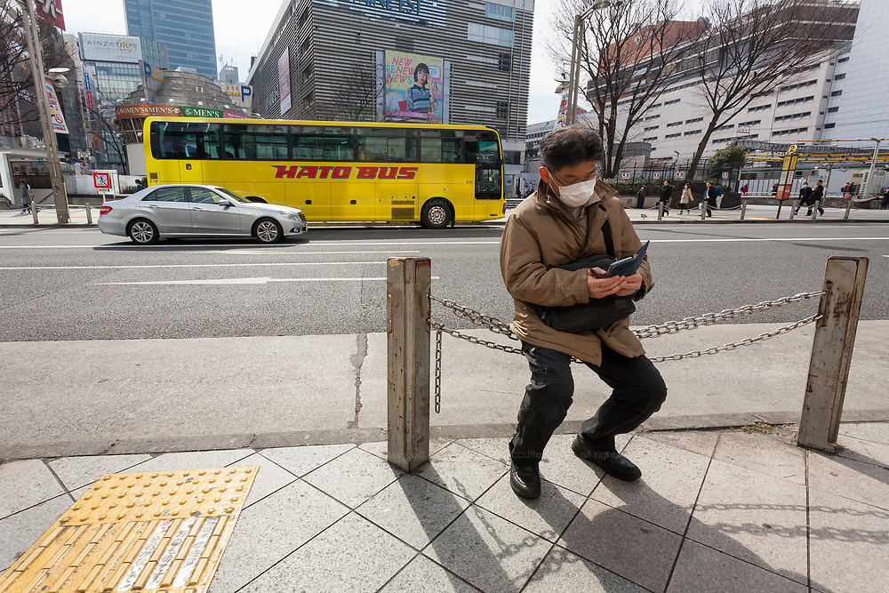 A Hato tour bus is seen behind a man checking his smart phone in Shinjuku. Tokyo, Japan. Friday February 22nd 2019