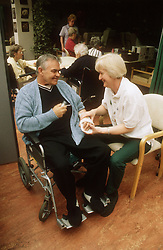 Man with disability; who is wheelchair user; talking with female occupational therapist,