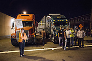 OAKLAND, CA - NOVEMBER 2, 2011: Occupy Oakland protesters exalt after they climb on top of a tractor trailer during their shutdown of the Port of Oakland., 2011: A female religious leader stands alone as a crowd of truck drivers wait to deliver their shipments to the Port of Oakland. The truck drivers were unable to complete their jobs and waited for hours as the Occupy Oakland movement shutdown the Port of Oakland.