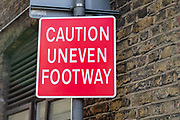 A Caution Uneven Footway sign seen on a pavement in east London, England on December 20, 2018