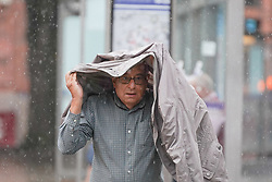 © Licensed to London News Pictures. 28/07/2021. Sheffield, UK. A man braves the rain in Sheffield as parts of Yorkshire are hit by heavy rain and thunderstorms. Photo credit: Ioannis Alexopoulos/LNP