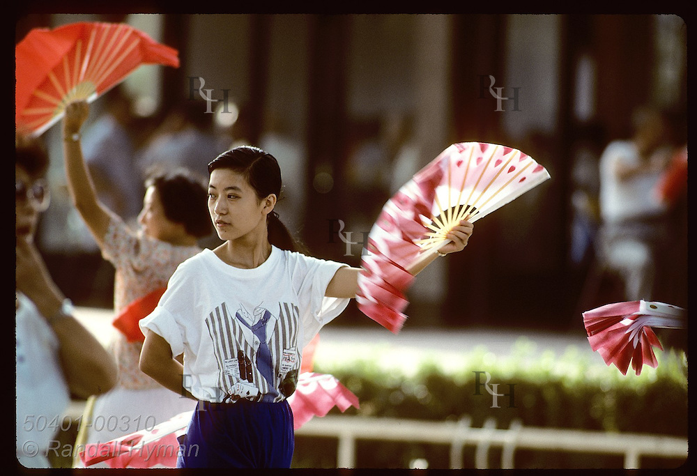 Young woman fan dances at early morning class in Jin An Park in central Shanghai. China