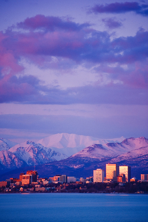 Alaska. Anchorage at sunset with Cook Inlet in the foreground and the Chugach Mtns beyond.