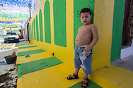 A yound boy stands on a colourfully decorated street corner opposite the Arena da Amazonia, Manaus, Brazil, ahead of the England v Italy World Cup 2014 group match. Photo by Andrew Tobin/Tobinators Ltd