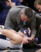BYU forward Noah Hartsock is treated by medical staff after getting hit in the face during the first half of an NCAA basketball game against Arizona, Dec. 11, 2010 in Salt Lake City. (AP Photo/Colin E Braley)