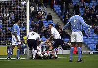Photo. Glyn Thomas.<br /> Manchester City v Tottenham Hotspur. FA Cup fourth round. <br /> City of Manchester Stadium, Manchester. 25/01/2004.<br /> Gary Doherty (C) is pulled from the ground after scoring Spurs' equaliser as Man City captain Sylvain Distin (R) objects.