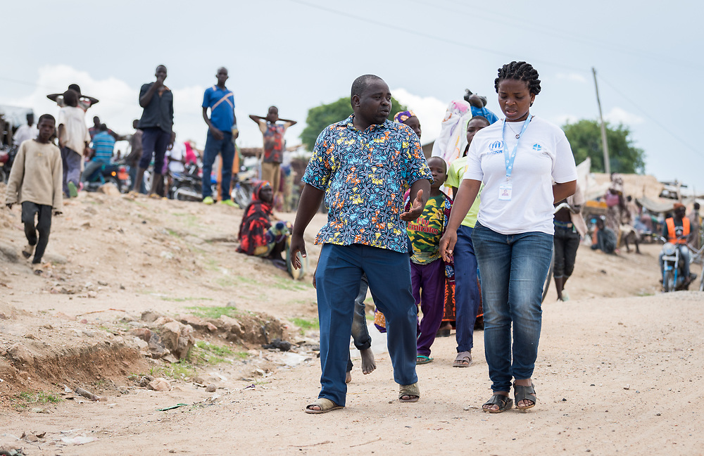 30 May 2019, Mokolo, Cameroon: Luka Isaac (left) serves as president of the central committee of the Nigerian refugees at Minawao. In this role, he undertakes the task of coordination of the refugees, as well as identifying and relaying the needs of the refugees to the partners engaged in service around the camp. 34-year-old Isaac arrived in the camp in 2014, from Gwoza, Nigeria, fleeing from the threat of Boko Haram. Here, he walks through Minawao together with Lutheran World Federation project coordinator Guilaine Tshatieu (right). The Minawao camp for Nigerian refugees, located in the Far North region of Cameroon, hosts some 58,000 refugees from North East Nigeria. The refugees are supported by the Lutheran World Federation, together with a range of partners.