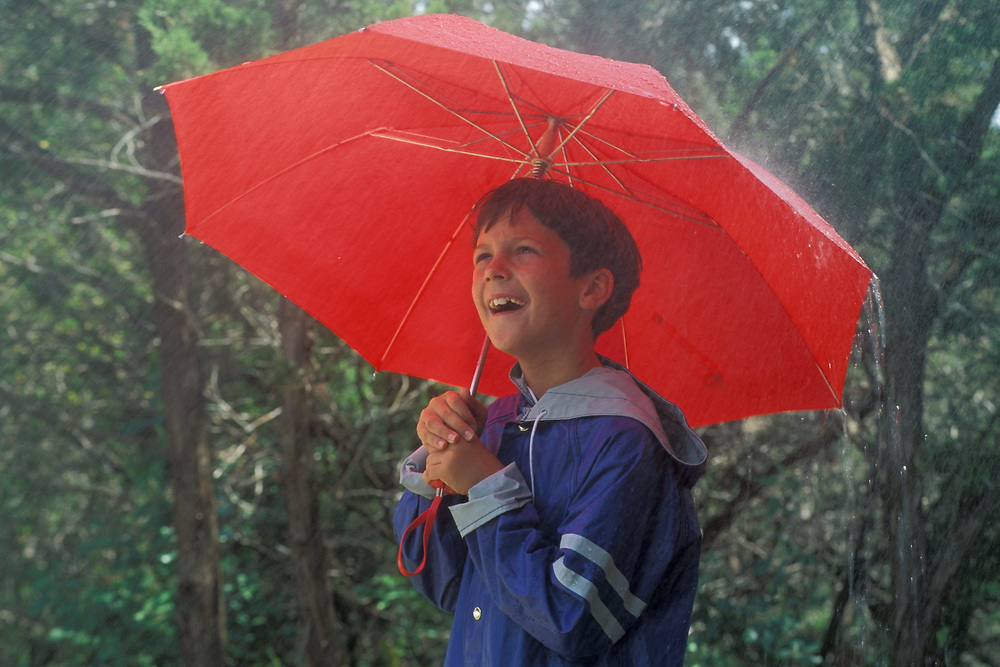 Young Anglo boy, 4th grader, standing outside in the rain while wearing blue rain jacket/pullover.  Model Release.