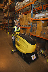 Man with a mild learning disability working as a factory cleaner, shown here with floor cleaning machine, helped into employment by the Ready 4 Work team, Nottinghamshire County Council