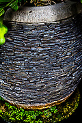 Stone pot with layers of small flat stones for a plant. Good for background.