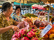 08 JUNE 2016 - BANGKOK, THAILAND:   Women shop for fresh fruit in the small street market at the intersection of Phlap Phla Chai and Chareon Krung Streets in Bangkok's Chinatown neighborhood. The Bangkok Metropolitan Rapid Transit (MRT) system, Bangkok's subway, is being expanded through Chinatown and a station is under construction at the intersection. The small produce market at the intersection will have to move and several of the businesses near the intersection have been evicted to make way for the construction. Bangkok's Chinatown, considered by some to be one of the best preserved Chinatown districts in the world, is changing. Many of the old shophouses are being demolished and replaced by malls and condominium developments.    PHOTO BY JACK KURTZ