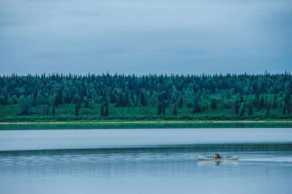 It was a quiet summer moring in the Tordrillo Mountains of Alaska when I shot this photo of Jillian Lukiwski paddleing her canoe along this glacial lake.