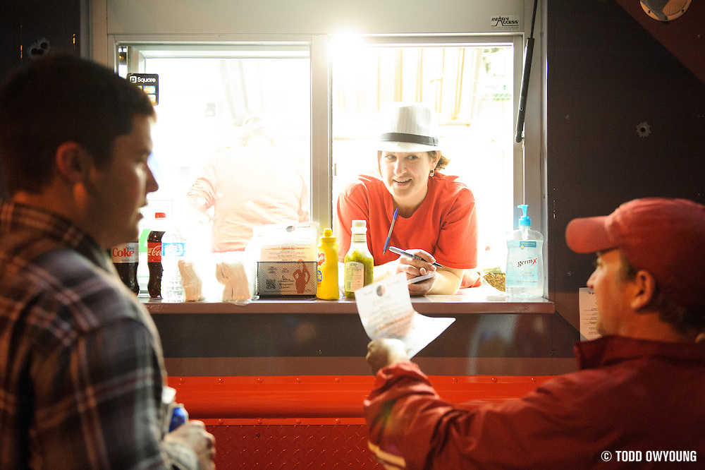 Fans grabbing a bite to eat at the Sausage Syndicate food truck parked on Market across from the Peabody Opera House.