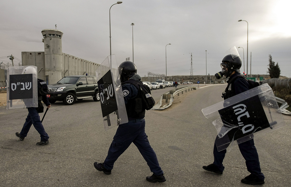 Israeli prison guards wearing gas masks and riot gear prepare to enter Ofer Prison, during clashes with Palestinian inmates at Ofer prison, near the West Bank city of Ramallah, on December 20, 2008. According to Israeli officials, seven Palestinian inmates and three Israeli prison guards were injured in the clashes, which broke after Palestinian inmates refused and forcefully resisted a search by prison authorities to the tents in which the inmates sleep in.