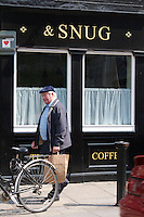 Senior man carrying paper shopping bag past a bar in Dublin Ireland