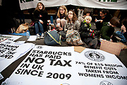 "London, UK. Saturday 8th December 2012. UK Uncut campaigners protest against tax avoidance by Starbucks. Despite the firm's pledge to pay millions of pounds of extra corporation tax for the next two years, over 40 of their coffee shops were part of a national demonstration. The organisers say the coffee company's promise to pay £20m is ""a desperate attempt to deflect public pressure"" from itself."