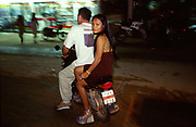 A Western man drives a bar girl on a motorcycle, on the Thai island of Koh Samui