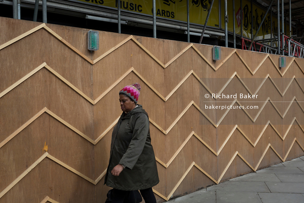 A lady wearing a similar patterned hat to the zigzag battens of a construction hoarding at Notting Hill, on 13th March 2018, in London, England.