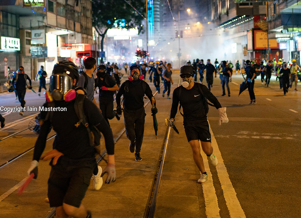 Hong Kong. 4 October 2019. Violent scenes in Hong Kong tonight with pro-democracy protestors vandalising shops and setting fire to the entrances of MTR stations. Protestors are angry with Chief Executive Carrie Lam's use of Emergency Powers to ban the wearing of masks during protests. Further demonstrations planned over the weekend. Pic; Protestors retreat from police charge and teargas attack in Causeway Bay. Iain Masterton/Alamy Live News.