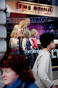 Showroom dummies in a window display for The Sting fashion outlet have blonde afros. Walking past a passer by has his own afro.