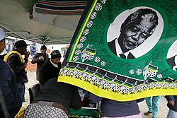 Wednesday 8th May 2019.<br /> Sinenjongo High School, Joe Slovo Park,<br /> Milnerton, Cape Town, <br /> Western Cape, <br /> South Africa.<br /> <br /> SOUTH AFRICAN GENERAL ELECTIONS 2019!<br /> <br /> SOUTH AFRICAN PROVINCIAL AND NATIONAL ELECTIONS 2019! <br /> <br /> An ANC political party members representatives table shows much activity as a printed cloth shows the image of Nelson Mandela and the official ANC logo, colours and emblems outside the voting station at Sinenjongo High School, Joe Slovo Park near Milnerton, Cape Town, Western Cape, South Africa.  <br /> <br /> Registered South African Voters head to the various IEC (Independent Electoral Commission) Voting Stations where they are registered to vote as they cast their votes and take part in voting and other activities on Voting Day 8th May 2019 during the South African General Elections 2019. Voters from across the nation stood in queue's along with many others to vote in the Provincial and National Elections being held in South Africa on Wednesday 8th May 2019.   <br />  <br /> Copyright © Mark Wessels. All Rights Reserved. No Usage Without Permission.<br /> <br /> PICTURE: MARK WESSELS. 08/05/2019.<br /> +27 (0)61 547 2729.<br /> mark@sevenbang.com<br /> studioseven@mweb.co.za<br /> www.markwesselsphoto.com