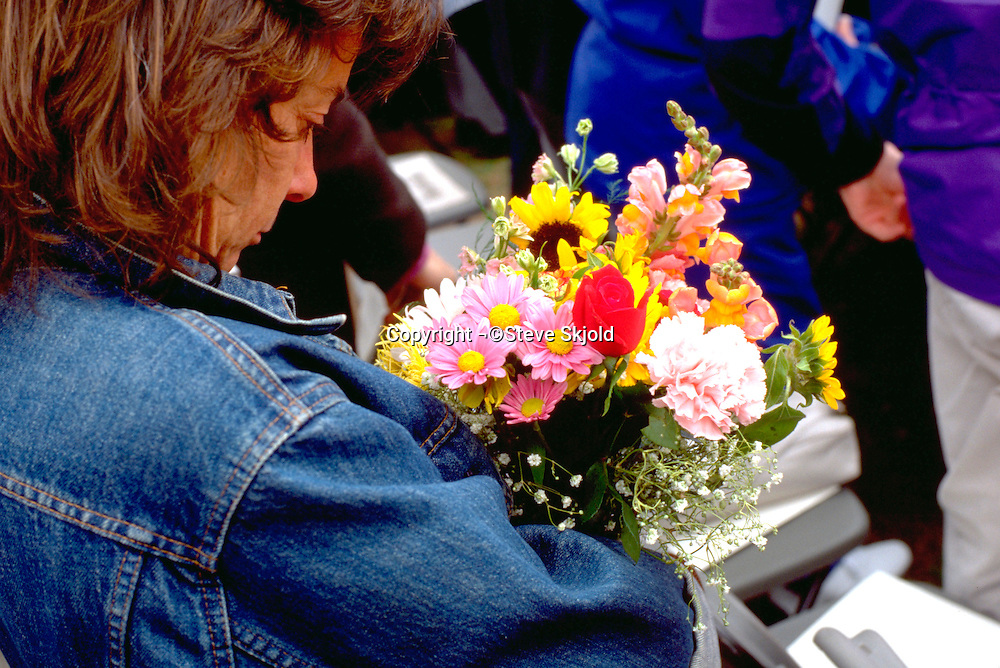 Mother age 40 holding bouquet at Macalester College graduation.  St Paul  Minnesota USA