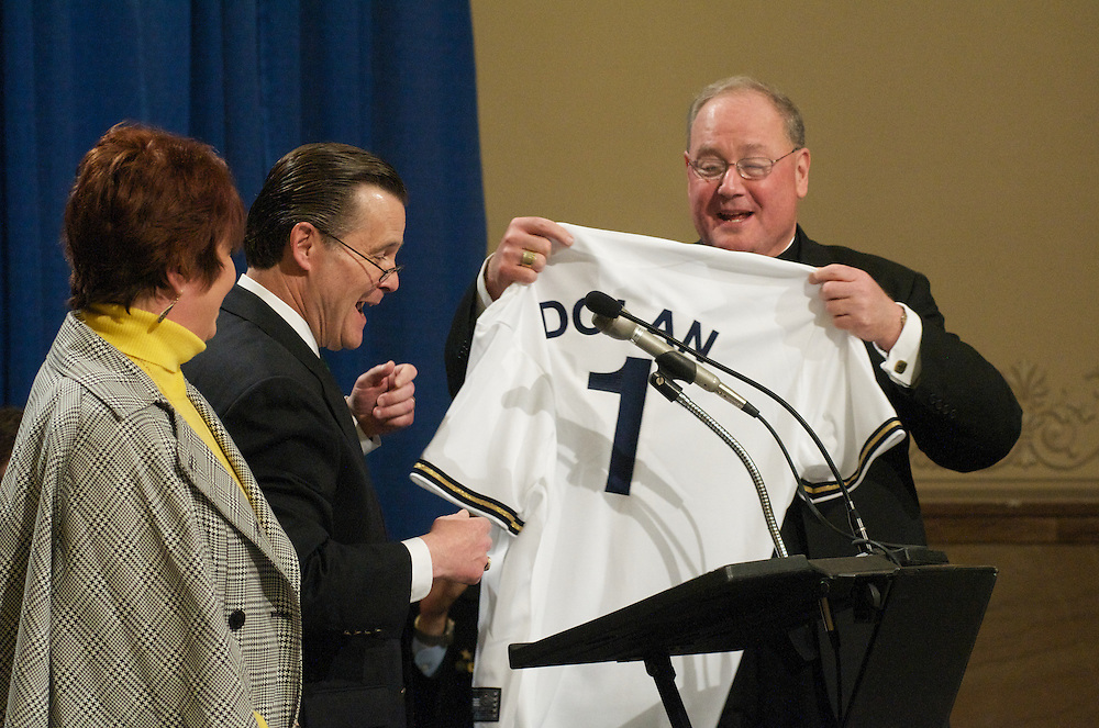 Alderman Bob Donovan and his wife Kathy present Archbishop Dolan with a Milwaukee Brewers jersey with his name on it as a gift at a farewell ceremony at City Hall, Tuesday March 31 2009.