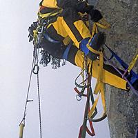 BAFFIN ISLAND, Nunavut, Canada. Greg Child (MR) makes awkward aid climbing moves during rain storm high on Great Sail Peak, an Arctic big wall climb above Stewart Valley.