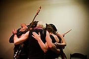 Kultur Shock gathers for their ritual pre-performance hug backstage at Gun Club in Belgrade, Serbia...