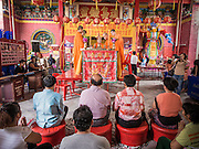 """09 AUGUST 2014 - BANGKOK, THAILAND:  A family sits in front of Vietnamese monks leading a service for Ghost Month at the Ruby Goddess Shrine in the Dusit section of Bangkok. The family sponsored the food give away and coordinated the cooking of the meals handed out. The seventh month of the Chinese Lunar calendar is called """"Ghost Month"""" during which ghosts and spirits, including those of the deceased ancestors, come out from the lower realm. It is common for Chinese people to make merit during the month by burning """"hell money"""" and presenting food to the ghosts. At Chinese temples in Thailand, it is also customary to give food to the poorer people in the community.       PHOTO BY JACK KURTZ"""