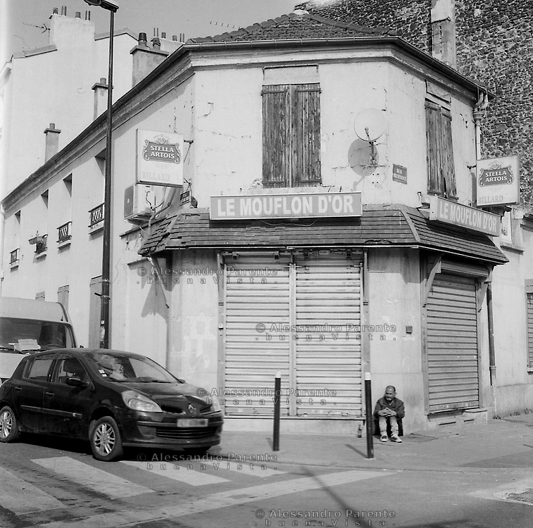 Aubervilliers, Seine Saint Denis. Bar are closed, an alcoholic is sitting outside his favourite place.