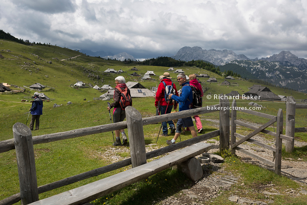 Walkers leave the chapel dedicated to Our Lady of the Snows, built in 1938 by the Slovenian architect Jože Plečnik, above the collection of Slovenian herders' mountain huts in Velika Planina, on 26th June 2018, in Velika Planina, near Kamnik, Slovenia. Velika Planina is a mountain plateau in the Kamnik–Savinja Alps - a 5.8 square kilometres area 1,500 metres (4,900 feet) above sea level. Otherwise known as The Big Pasture Plateau, Velika Planina is a winter skiing destination and hiking route in summer. The herders' huts became popular in the early 1930s as holiday cabins (known as bajtarstvo) but these were were destroyed by the Germans during WW2 and rebuilt right afterwards by Vlasto Kopac in the summer of 1945.