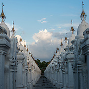 Rows of kyauksa gu, each housing a stone tablet of text, at Kuthodaw Pagoda. Built by King Mindon in 1857 at the foot of Mandalay Hill, Kuthodaw Pagoda houses what is known as The World's Largest Book, which consists of 729 kyauksa gu or stone-inscription caves, each containing a marble slab inscribed on both sides with a page of text from the Tipitaka, the entire Pali Canon of Theravada Buddhism.