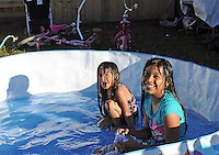 On a hot blue afternoon, four year-old Norali Perez of east Salinas splashes around after-school with her sister Maria, a Loma Vista 5th grader, in a pool filled up just for the occasion.