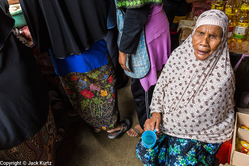 09 JULY 2013 - PATTANI, PATTANI, THAILAND:  A blind Muslim woman begs in the market in Pattani.  Pattani, along with Narathiwat and Yala, are the only three Muslim majority provinces in Thailand.     PHOTO BY JACK KURTZ