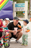2 1/2 year old Aden Azkul enjoys some popcorn along with his dad Bassem during the 2nd annual WOW Fest activities at Laconia Athletic and Swim Club on Saturday.  (Karen Bobotas/for the Laconia Daily Sun)