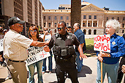 09 MAY 2011 - PHOENIX, AZ: An Arizona Capitol Police Officer steps between MANUEL MARTINEZ, left, an immigrants' rights supporter, and KATHRYN KOBOR, as they argue about illegal immigration at the Arizona State Capitol in Phoenix Monday. Governor Jan Brewer, State Senate President Russell Pearce and Attorney General Tom Horne, all Republicans, held one press conference to announce that the state was suing to take its legal battle over SB1070, Arizona's tough anti-immigration law, past the US Court of Appeals and straight to the US Supreme Court. State Senator Steve Gallardo, a Democrat, held a press conference to announce that he was opposed to the Republican's legal actions and called on them to drop the suit altogether. Isolated shouting matches broke out between activists on both sides of the immigration issue during the press conferences.       Photo by Jack Kurtz